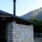 薪ストーブの煙突と石壁